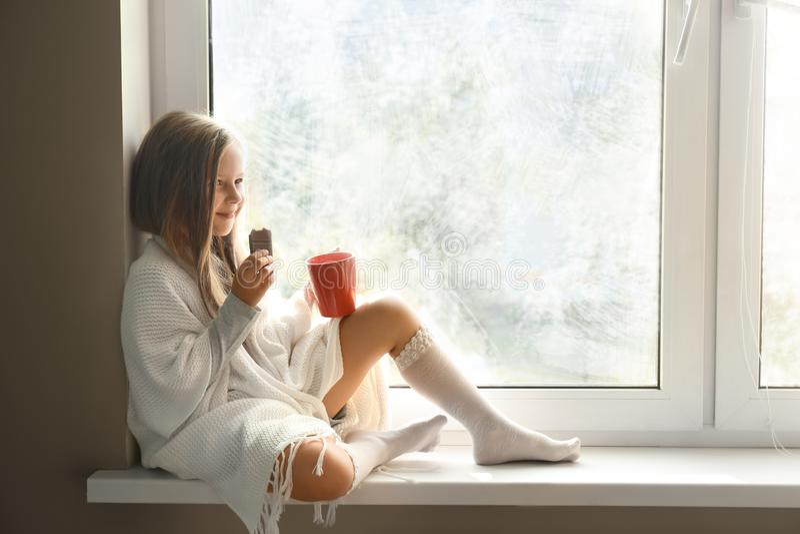 Menina bonito envolvida na manta morna com o copo da bebida quente do cacau que come o chocolate na soleira em casa foto de stock