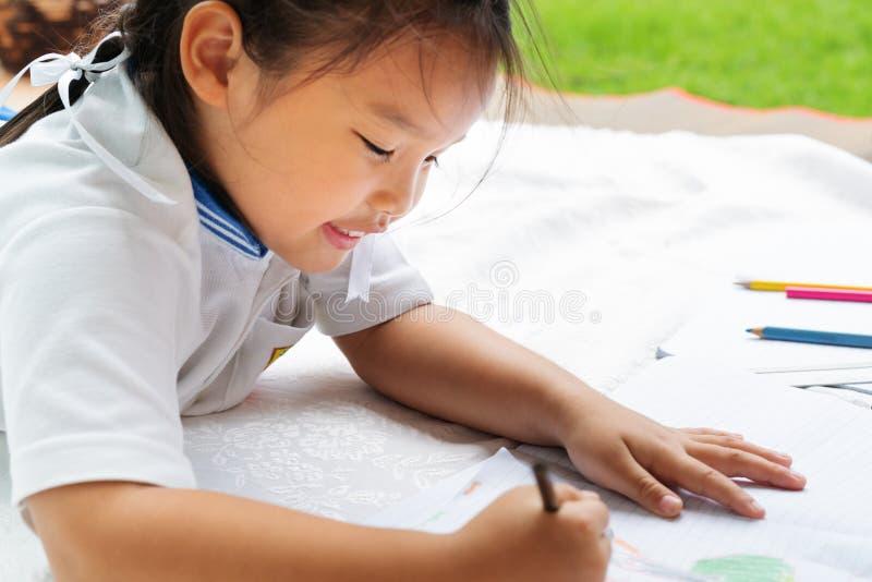 A menina bonito escreve aos escrita-livros A decisão das lições a menina estabelece a tiragem da imagem foto de stock royalty free