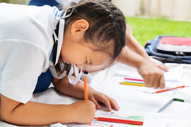 A menina bonito escreve aos escrita-livros A decisão das lições a menina estabelece a tiragem da imagem fotos de stock royalty free