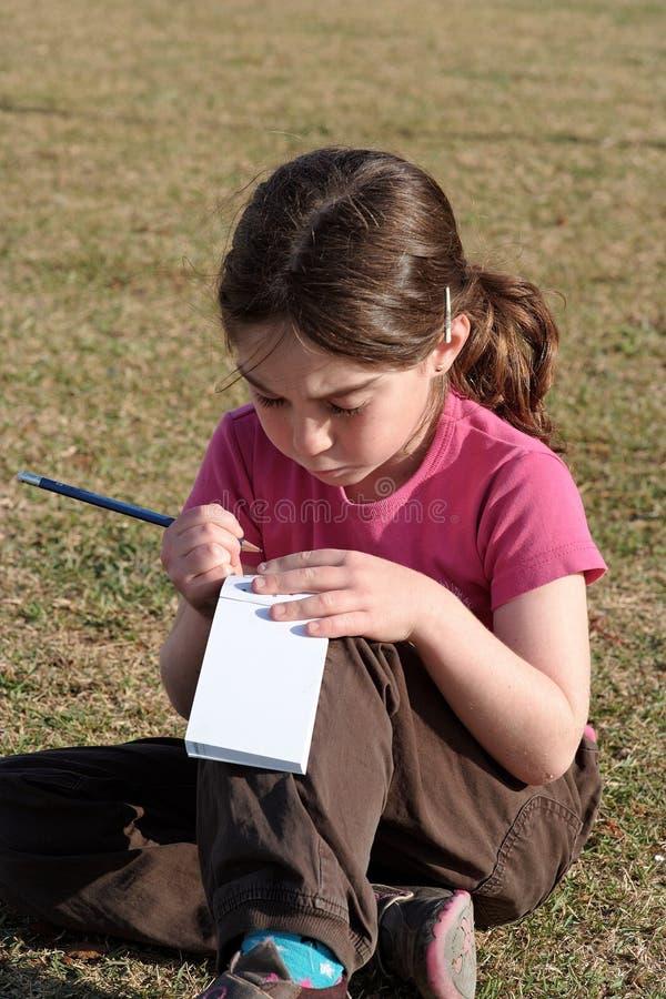 A menina bonito escreve o assento na grama fotografia de stock