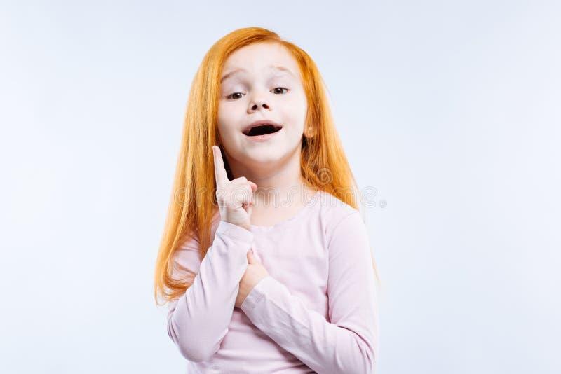 Menina bonito esperta agradável que tem uma ideia fotografia de stock