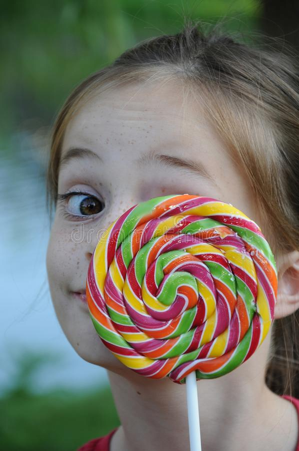 A menina bonito espreita atrás de um lolly gigante imagem de stock royalty free