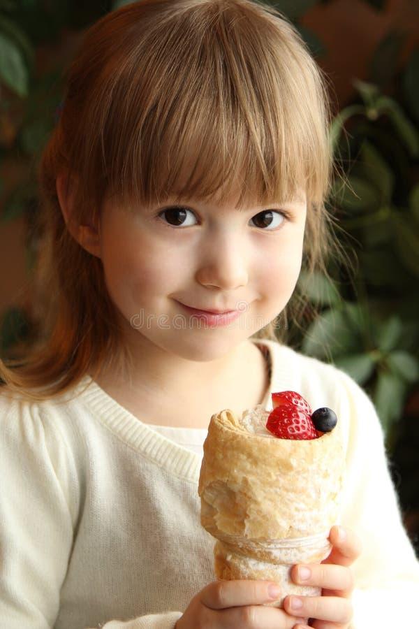 A menina bonito está comendo o bolo fotografia de stock