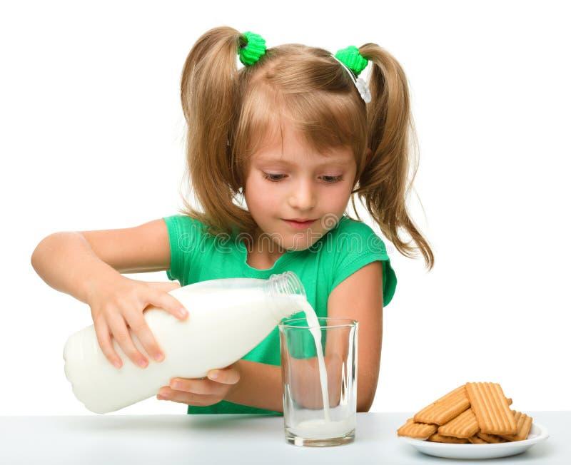 A menina bonito está derramando o leite no vidro imagens de stock royalty free