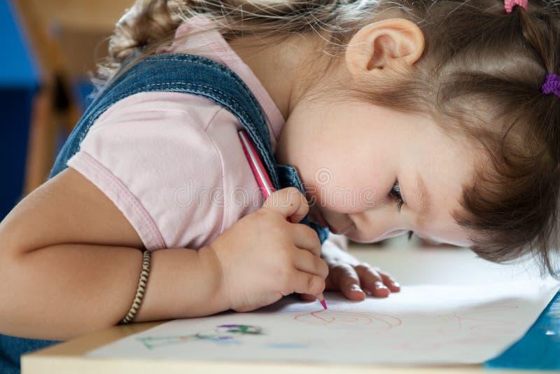 A menina bonito está desenhando com a pena no pré-escolar fotografia de stock