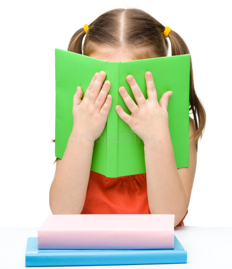 A menina bonito está escondendo atrás de um livro fotografia de stock