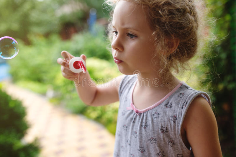 A menina bonito está fundindo as bolhas de sabão, fim acima da foto fotos de stock