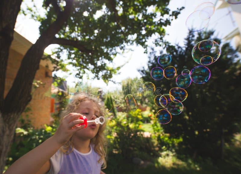 A menina bonito está fundindo bolhas de sabão foto de stock royalty free