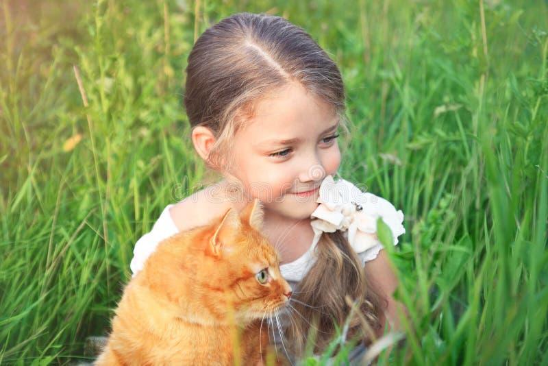 A menina bonito está guardando um gato vermelho que senta-se na grama fotografia de stock royalty free