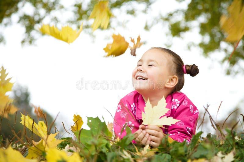 A menina bonito está jogando com as folhas no parque foto de stock royalty free