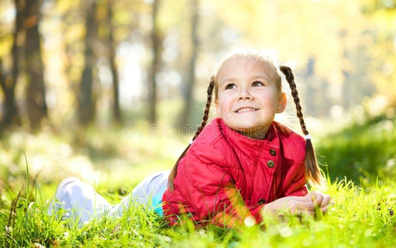 A menina bonito está jogando com as folhas no parque imagem de stock