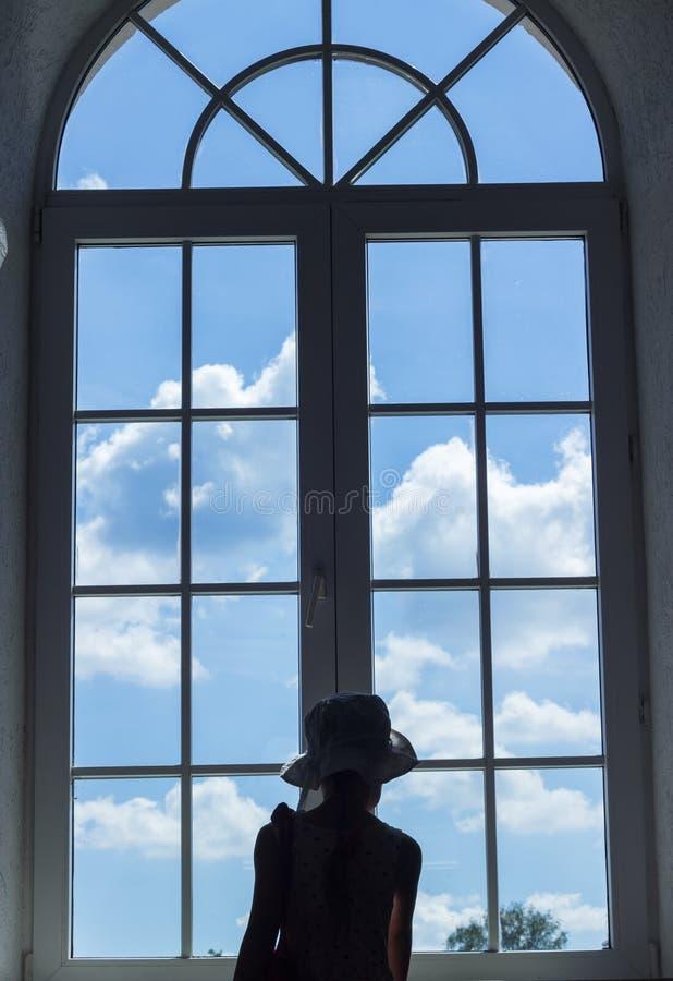 A menina bonito está perto de uma janela e olha o céu com nuvens imagem de stock