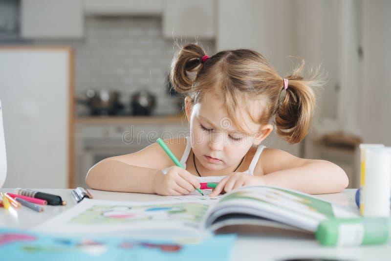 A menina bonito está tirando com caneta com ponta de feltro em casa imagens de stock royalty free