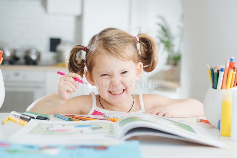 A menina bonito está tirando com caneta com ponta de feltro em casa foto de stock royalty free