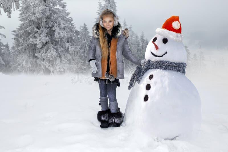 A menina bonito, estando na neve e faz um boneco de neve com neve A menina é vestida na roupa do inverno imagens de stock