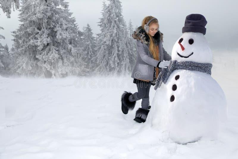 A menina bonito, estando na neve e faz um boneco de neve com neve A menina é vestida na roupa do inverno fotos de stock royalty free