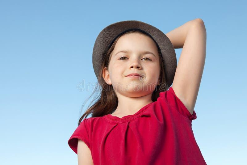 Menina bonito exterior vestindo uma camisa vermelha e um chapéu imagens de stock