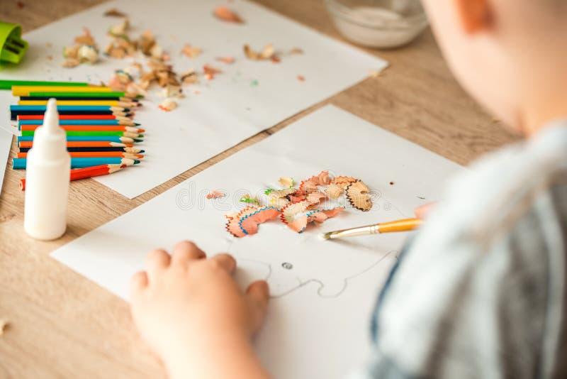 A menina bonito faz o applique cola a casa colorida, aplicando o papel da cor usando a colagem ao fazer artes e ofícios no pré-es fotos de stock