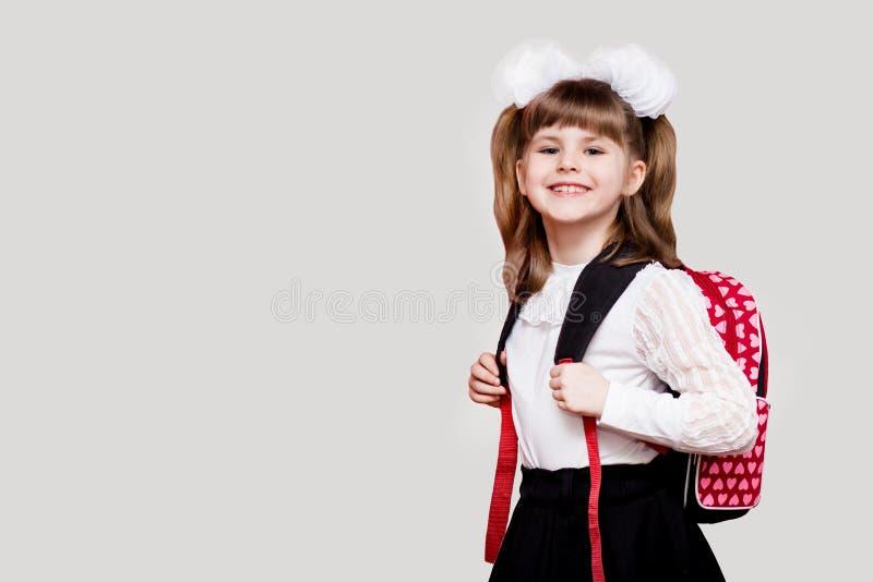 Menina bonito feliz da crian?a com o saco de escola isolado em um fundo branco Primeira vez ? escola fotos de stock royalty free