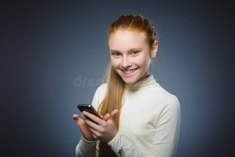 Menina bonito feliz do ruivo com telefone celular Isolado no cinza imagem de stock