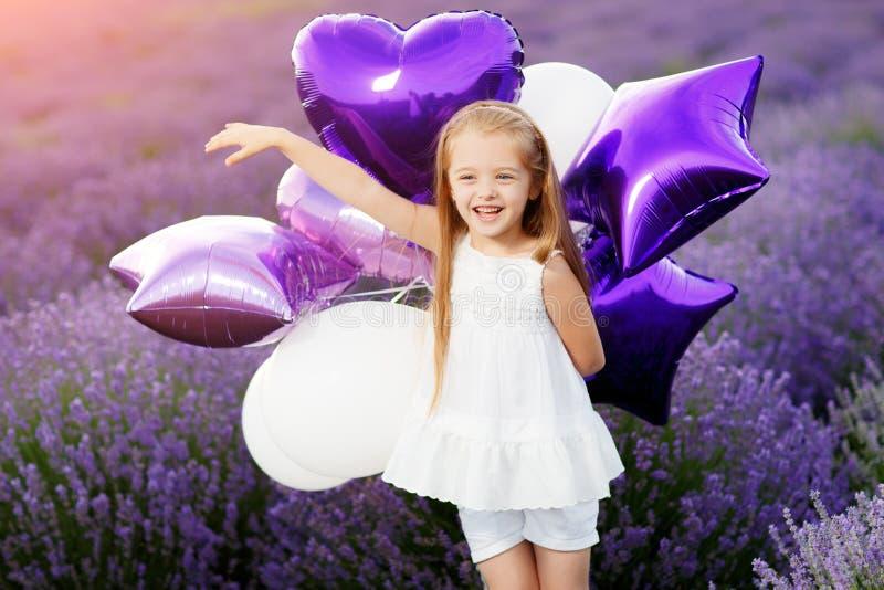 Menina bonito feliz no campo da alfazema com balões roxos Conceito da liberdade imagens de stock