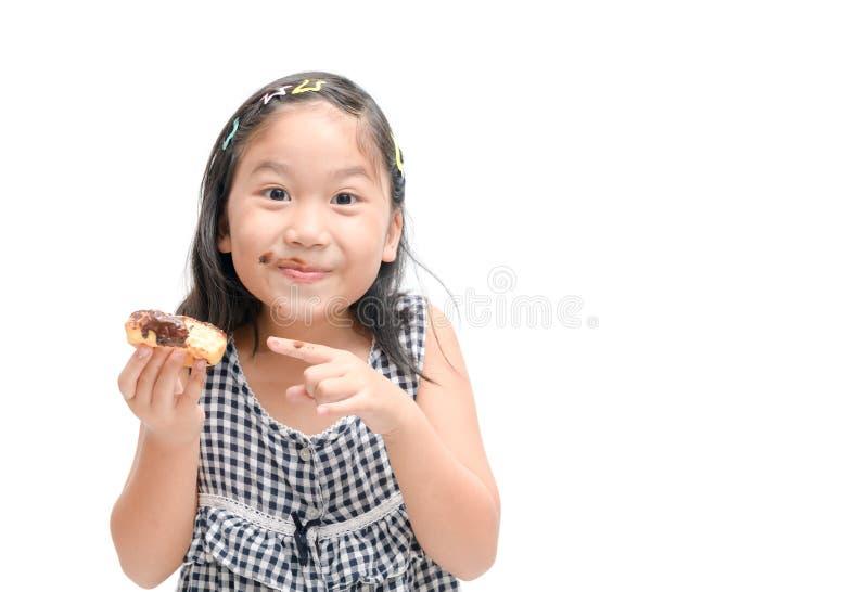 A menina bonito feliz pequena está comendo a filhós isolada foto de stock