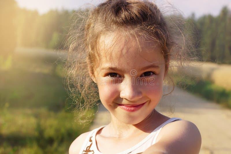 Menina bonito feliz que faz o selfie sobre o parque ensolarado Menina bonito do Preteen imagem de stock royalty free