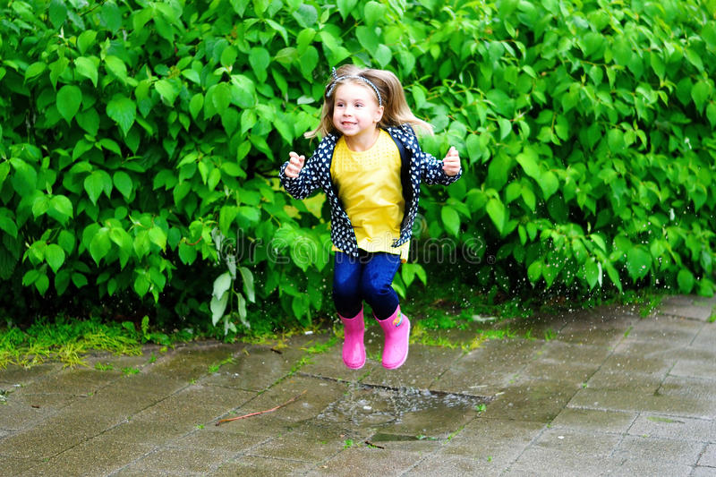 Menina bonito feliz que salta na poça após a chuva no verão fotos de stock royalty free