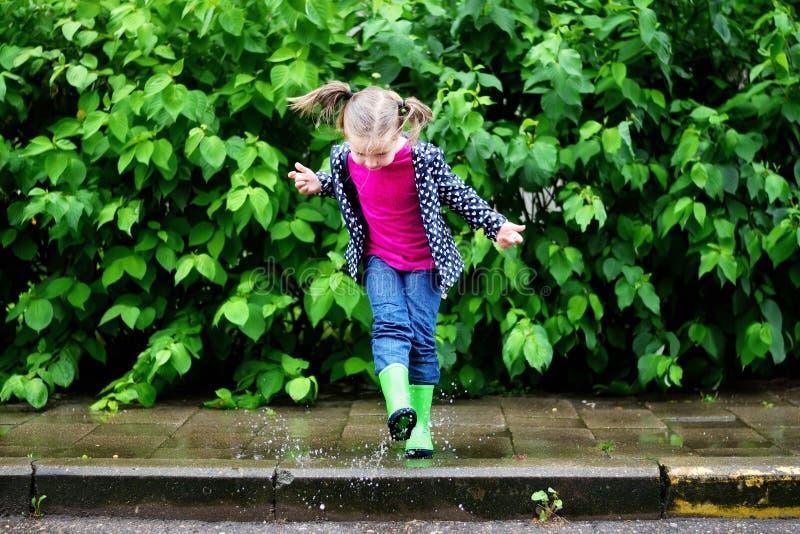 Menina bonito feliz que salta na poça após a chuva no verão imagens de stock royalty free