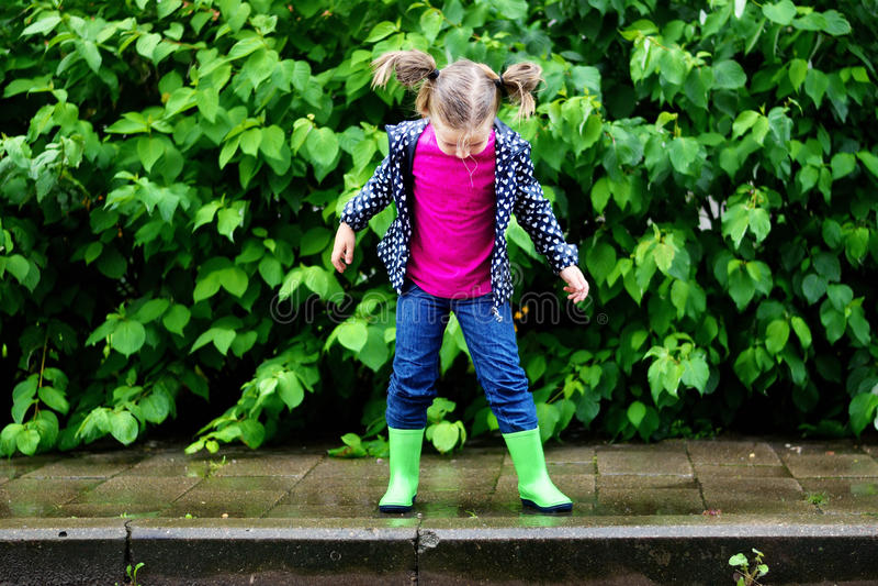 Menina bonito feliz que salta na poça após a chuva no verão foto de stock