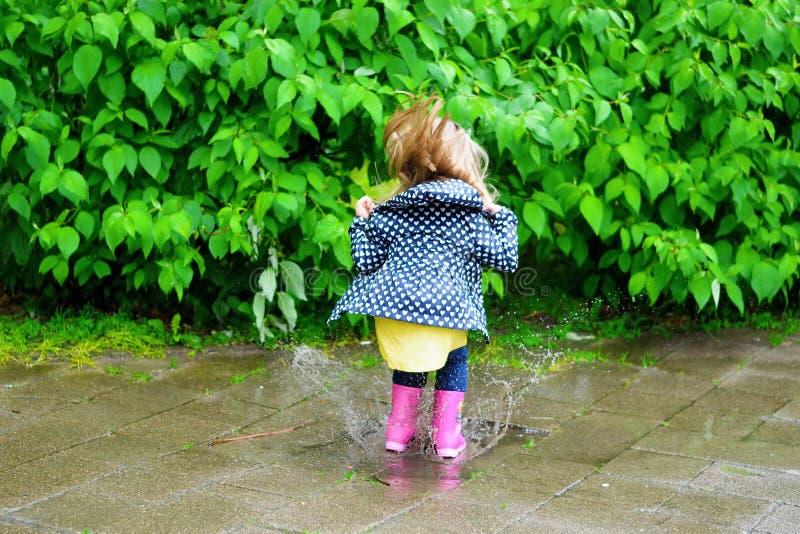 Menina bonito feliz que salta na poça após a chuva no verão fotografia de stock royalty free