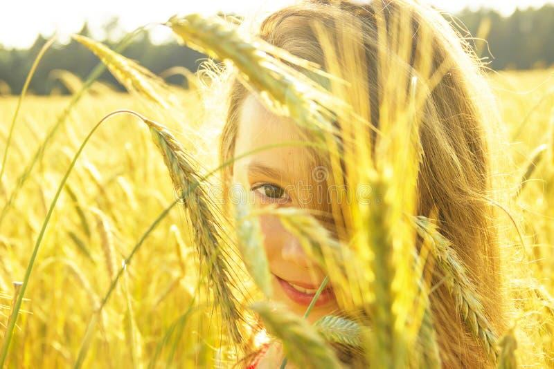 Menina bonito feliz que sorri no campo no por do sol Menina feliz na natureza imagens de stock royalty free