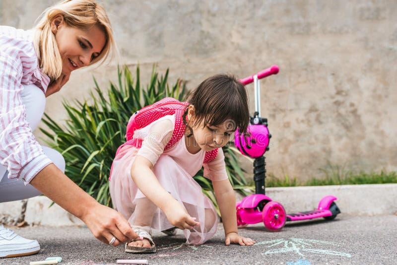 A menina bonito feliz veste o desenho do vestido e da mãe com gizes coloridos no passeio Jogo fêmea caucasiano junto com fotos de stock royalty free