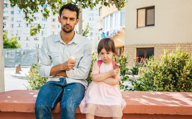Menina bonito infeliz que senta-se com o paizinho na rua da cidade e que come o gelado exterior A criança da menina da virada e o foto de stock