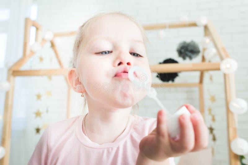 A menina bonito joga com bolhas de sab?o imagem de stock