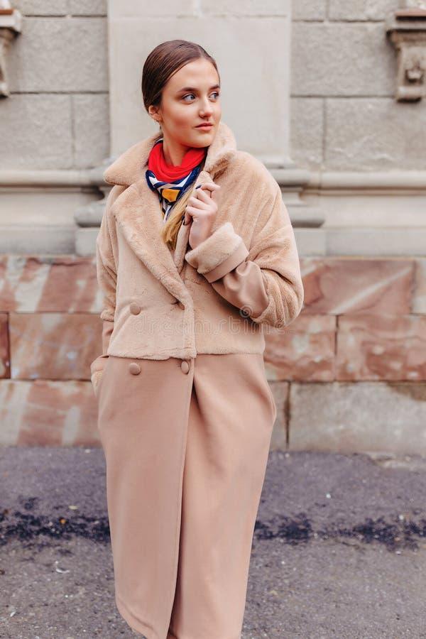 Menina bonito ? moda nova em um casaco de pele que d? uma volta em torno da cidade perto das casas de madeira e das paredes de pe foto de stock