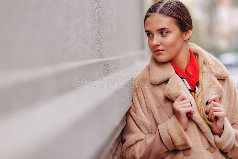 Menina bonito ? moda nova em um casaco de pele que d? uma volta em torno da cidade perto das casas de madeira e das paredes de pe fotografia de stock