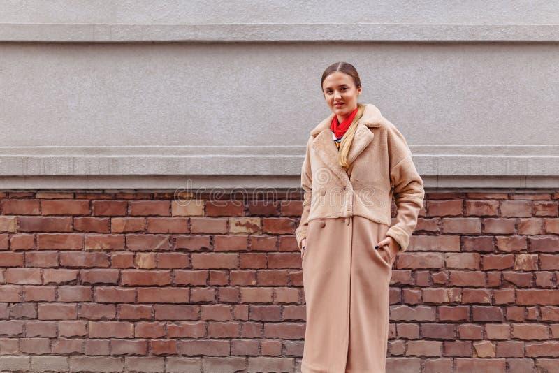 Menina bonito ? moda nova em um casaco de pele que d? uma volta em torno da cidade perto das casas de madeira e das paredes de pe fotos de stock