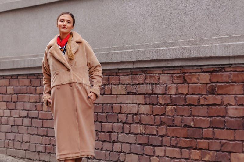 Menina bonito ? moda nova em um casaco de pele que d? uma volta em torno da cidade perto das casas de madeira e das paredes de pe foto de stock royalty free