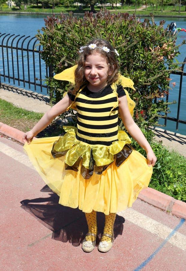 A menina bonito não identificada com tropeça o traje da abelha que levanta no carnaval alaranjado da flor foto de stock