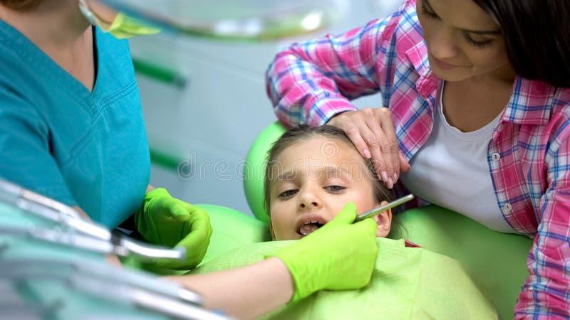 Menina bonito na cadeira da odontologia no exame regular, filha da terra arrendada da mãe imagens de stock royalty free