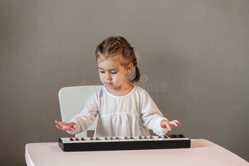 Menina bonito na camisa branca que joga o piano eletrônico fotos de stock royalty free