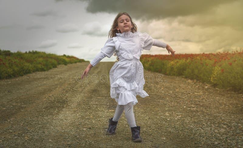 Menina bonito na dança branca do vestido na natureza imagens de stock royalty free