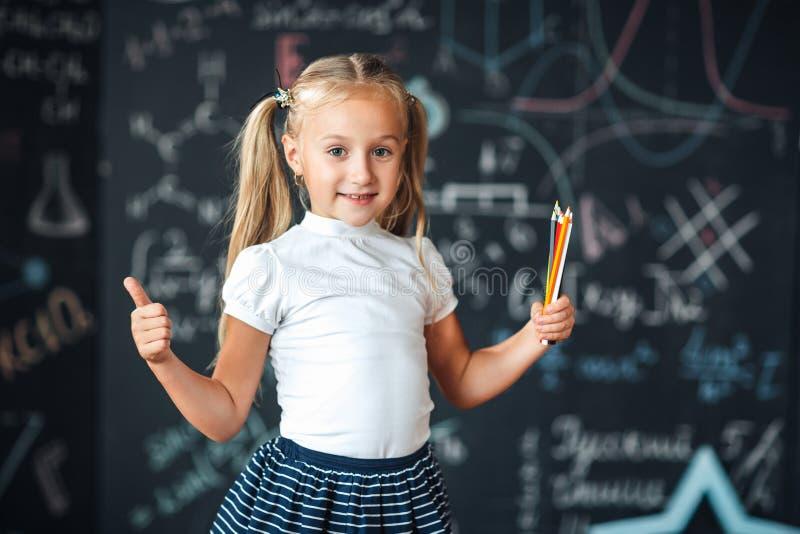 Menina bonito na farda da escola com lápis coloridos Vá educar pela primeira vez Menina dentro da sala de classe com quadro-negro fotos de stock