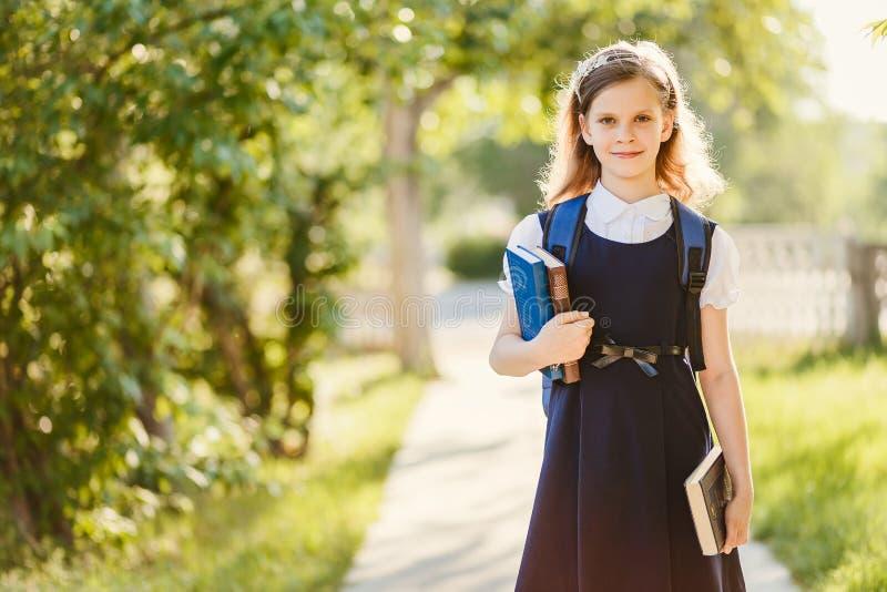 Menina bonito na farda da escola com livros fora, sunligh contrário fotos de stock royalty free