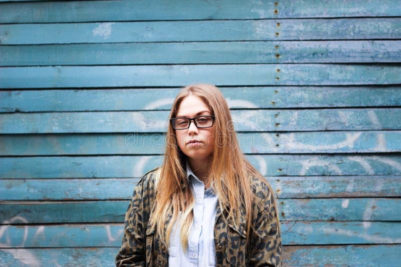 Menina bonito na frente de uma parede de madeira azul imagem de stock royalty free