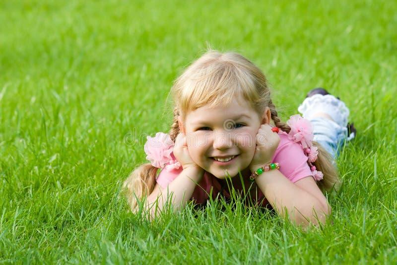 Menina bonito na grama. imagens de stock royalty free