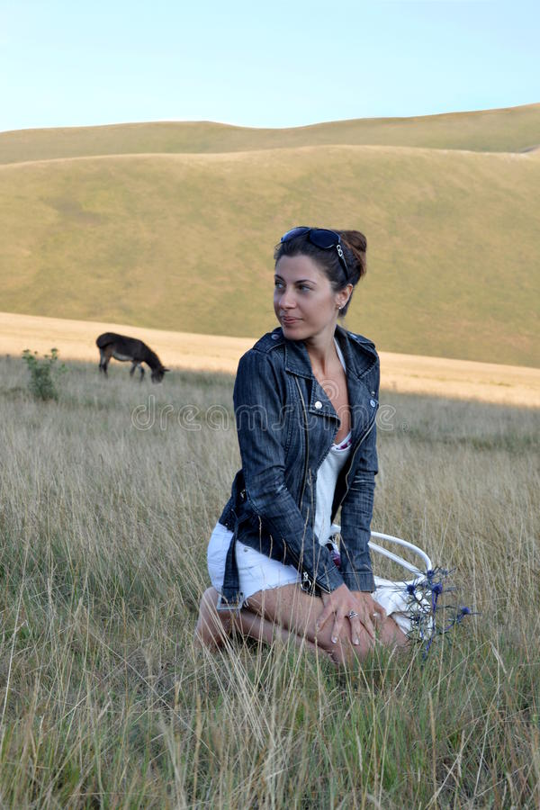 Menina bonito na montanha e em uma flor fotografia de stock royalty free