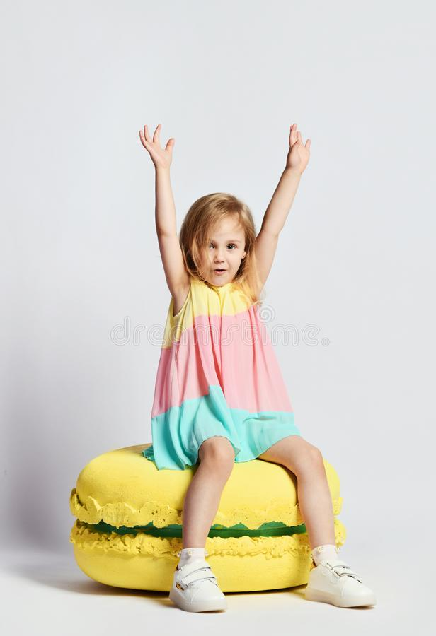 A menina bonito na roupa brilhante tem o divertimento nos macarons dos doces da decoração da sala do divertimento da festa de ano foto de stock