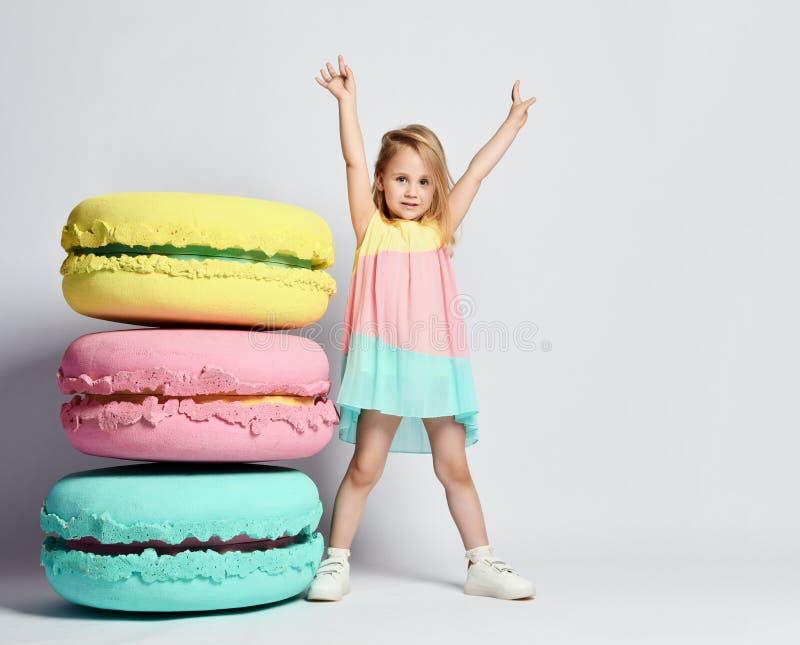 A menina bonito na roupa brilhante tem o divertimento nos macarons dos doces da decoração da sala do divertimento da festa de ano imagem de stock